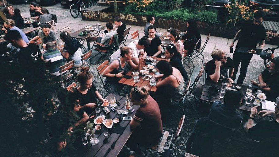 Junge Menschen sitzen im Biergarten mit einem Bier.