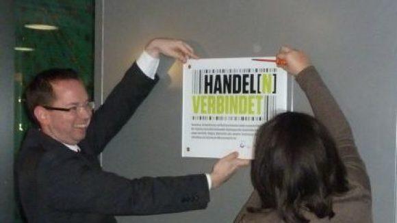 """Bürgermeister Oliver Igel und Senatorin Dilek Kolat befestigen das Schild zur Kampagne """"Handel[n] verbindet"""" im Eingangsbereich des Zentrums Schöneweide."""