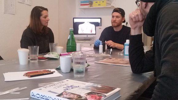 Teilnehmer hören Leiter beim Poke Tattoo Workshop zu.