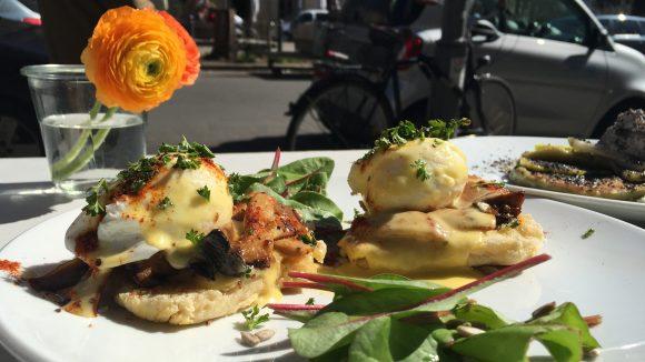 Eggs Benedict auf Teller mit Salat-Deko und Blume im Hintergrund
