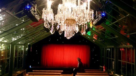Ein Kronleuchter, Holzbänke und der neue rote Vorhang im Glaspalast vom Pfefferberg Theater. ©QIEZ