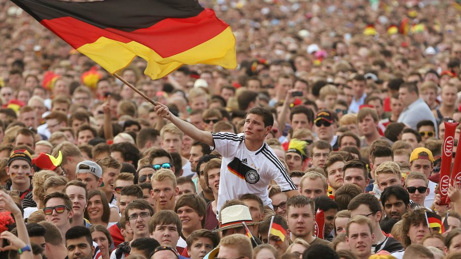 Ein Fan der Nationalmannschaft schwingt eine Deutschland Fahne in einem Meer aus Fans