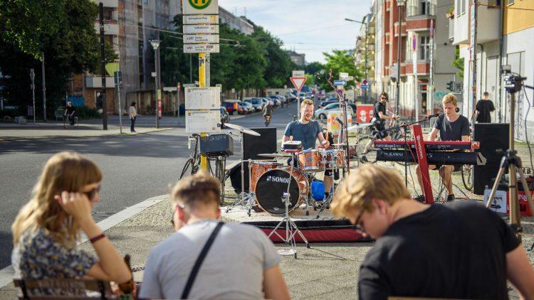 Musiker mit Instrumenten auf der Straße an der Bushaltestelle