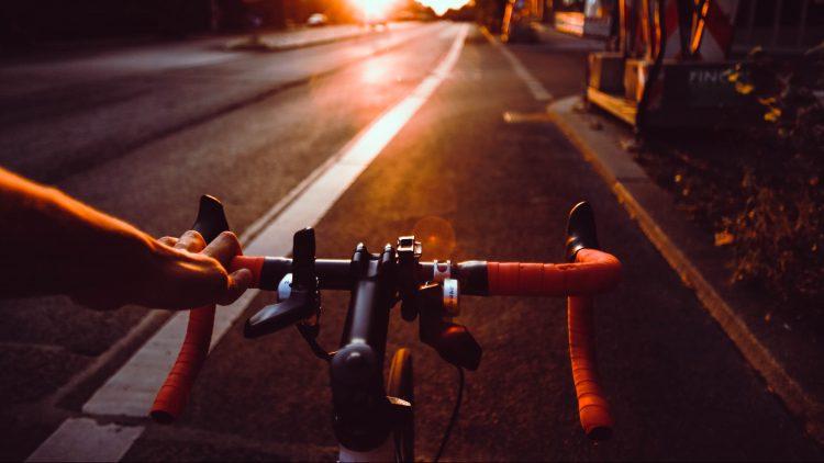 Fahrradlenker mit Blick auf Straße in der Großstadt bei Sonnenuntergang