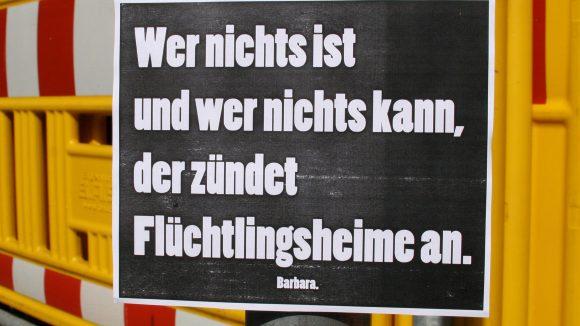 """Plakat mit Aufschrift """"Wer nichts ist und wer nichts kann, der zündet Flüchtlingsheime an"""""""