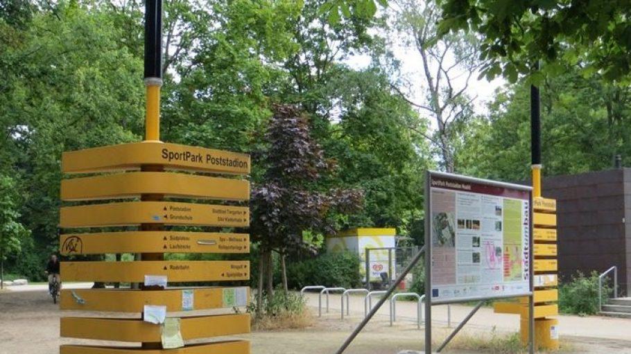 """Der Haupteingang zum Fritz-Schloß-Park in der Rathenower Straße. Auf den Schildern wird der Park einfach nur als """"SportPark Poststadion"""" bezeichnet."""