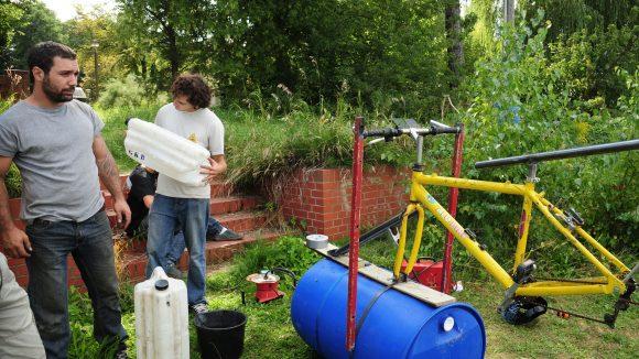 Hier bauen zwei Teilnehmer an einem Boot für die Schrottregatta - aus alten Fahrrädern und Regentonnen.
