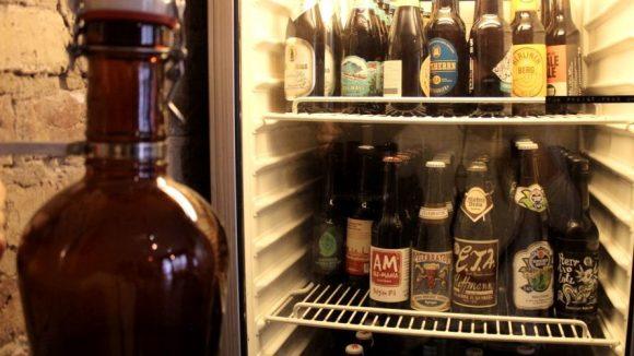 """Alte Bügel-Glaschflasche zum Abfüllen von Bieren im Biershop """"Lager Lager"""" vor dem Kühlschrank für Flaschenbiere."""