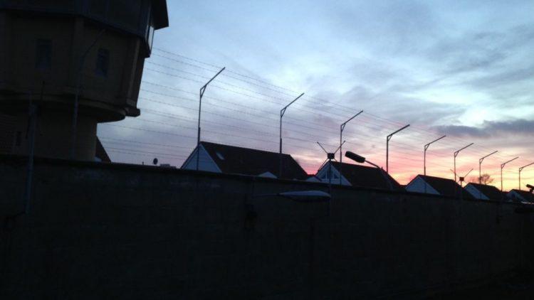 Hinter der Gefängnismauer der Gedenkstätte Hohenschönhausen geht die Sonne unter.