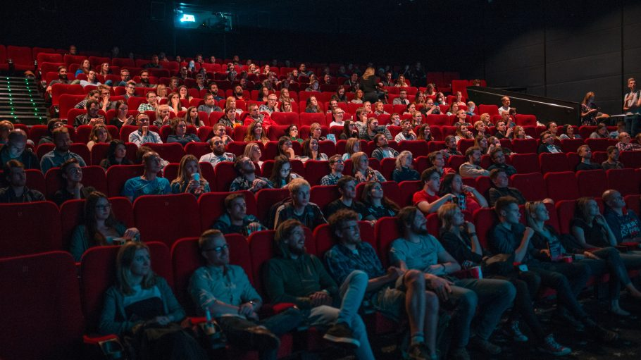 Menschen im Kino sitzen in roten Sesseln