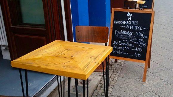 Tische, Stühle und Tafel mit Speisekarte auf dem Gehsteig vor dem Haferkater.