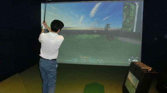 Clubleiter Kim macht es vor: Die Golfbälle schlägt man wie im Freien mit professioneller Ausrüstung quer über den virtuellen Rasen. Vorteil: Sie prallen an der Wand ab und rollen automatisch zurück in die Ballanlage, die die Spieler automatisch mit Nachschub versorgt.