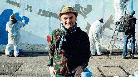 Provokante Aktion. Da lacht er noch: Vor drei Wochen entschied Jim Avignon, zusammen mit Studenten sein Bild an der East Side Gallery zu übermalen. Die Kritik folgte zugleich.