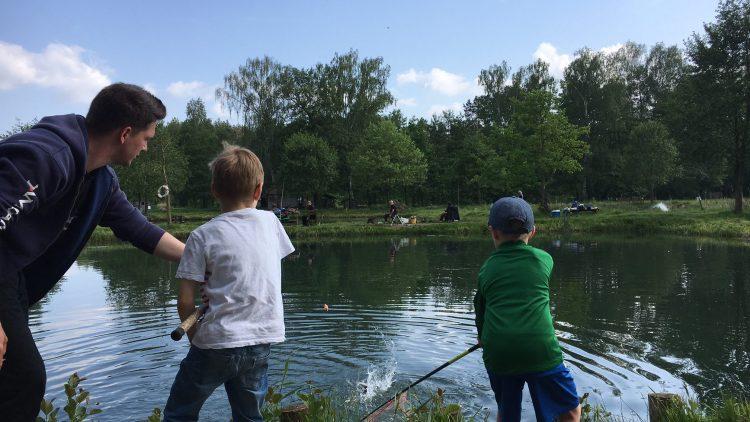 Zwei Jungen und ein Angel-Guide am Ufer eines Fischteichs