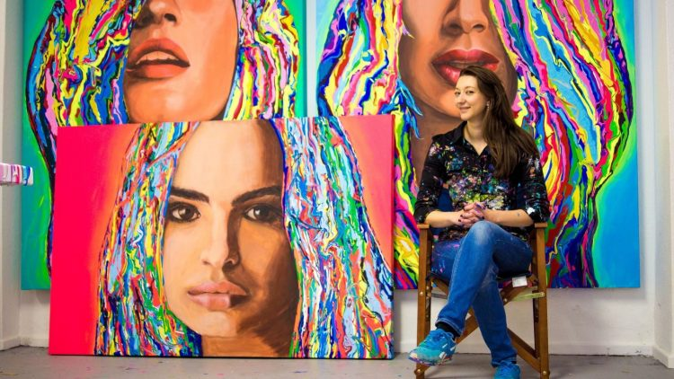 Künstlerin Yelizavyeta präsentiert stolz ihre knalligen Kunstwerke. Wer's nicht erkennt: Links oben ist Gisele Bündchen.