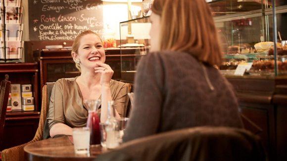 Marlene lacht herzlich im Café.