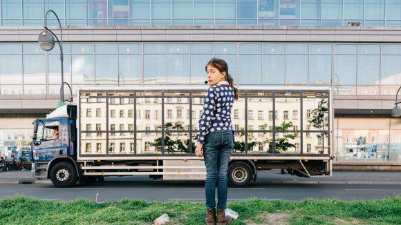 Mädchen steht vor einem verspiegeltem LKW