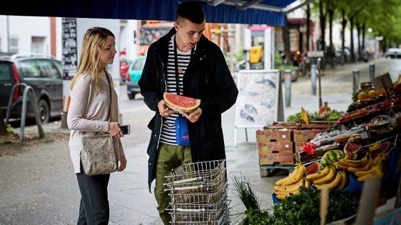 Vor einem Obsthändler in Charlottenburg. mauli hält eine Wassermelone in Hand.