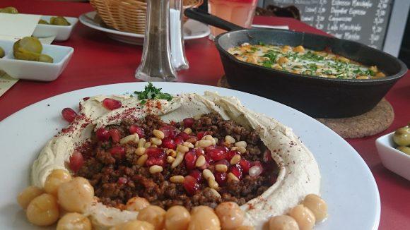Israelische Gerichte: Humus mit Rinderhack und Granatapfel und Shakshuka in der Pfanne.Neben dem international beliebten Hauptgericht gibt es auch weitere Spezialitäten, wie Rinderhack in Humus mit Granatapfel, der so hervorragend schmeckt, wie er aussieht!