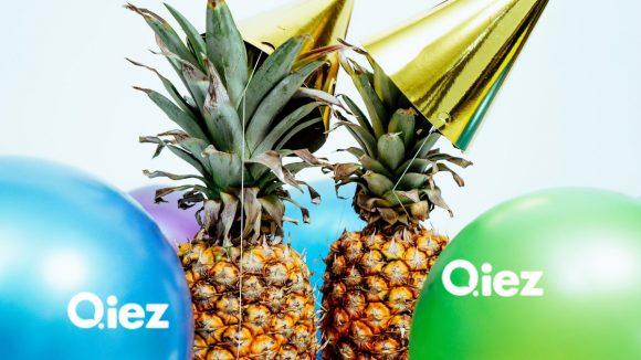Ananas mit Partyhüten und bunten Ballons zur Feier des Relaunch von QIEZ