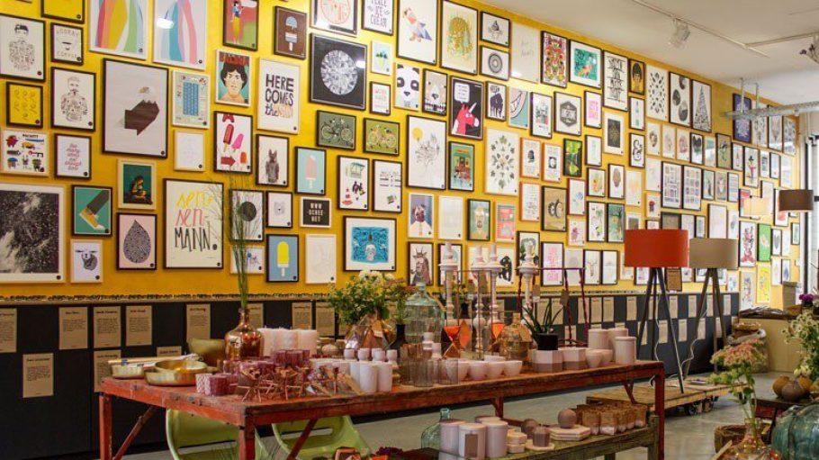 """Viele bunte Bilder hängen an den gelben Wänden vom Kunst-Shop """"Schee"""" in Mitte."""