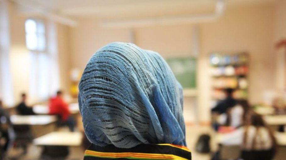 Ein Mädchen sitzt mit Kopftuch im Unterricht. Eine Schuldirektorin aus Wilmersdorf wollte das verbieten.