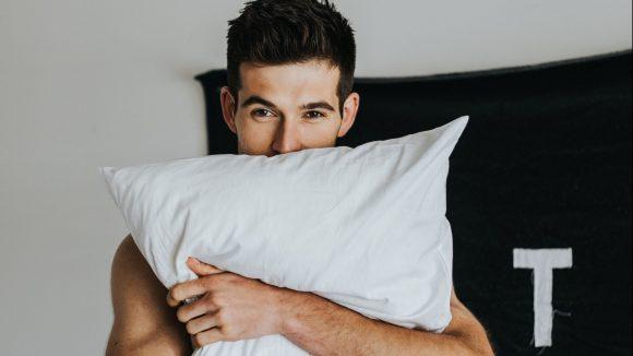 Junger sexy Typ in Unterhose bedeckt seinen Oberkörper mit einem Kissen