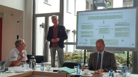 Professor Jürgen Rode von der Universität Potsdam stellt das Planungsverfahren vor. Mit am Tisch: Bezirksbürgermeister Stefan Komoß (r.) und Frank Kolbe (l.) vom Schul- und Sportamt Marzahn-Hellersdorf.