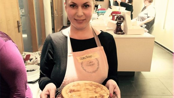 """Stolz präsentiert Gerlinde den """"Maple Walnut Cheesecake"""", den sie unter der Anleitung von Cynthia Barcomi gebacken hat."""