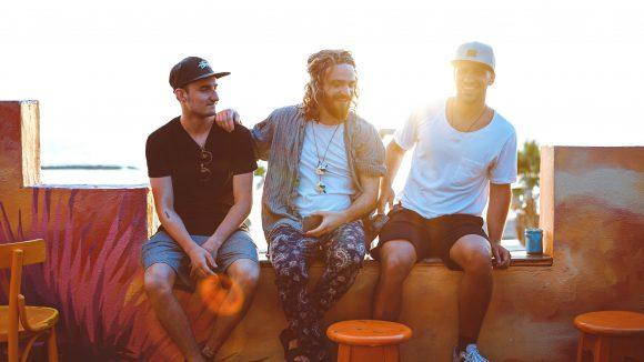 Drei Männer sitzend im Gegenlicht