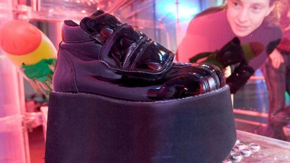"""Museumsreferentin Barbara Sydow blickt am Mittwoch (04.11.2009) im Rock 'n' Popmuseum in Gronau (Kreis Borken) auf Plateauschuhe. """"Techno - ein Blick zurück in die Zukunft"""" heißt die Sonderausstellung, die vom Sonntag (08.11.2009) bis zum Sonntag (18.04.2010) - anläßlich des zwanzigsten Jubiläums der ersten Loveparade - gezeigt wird."""