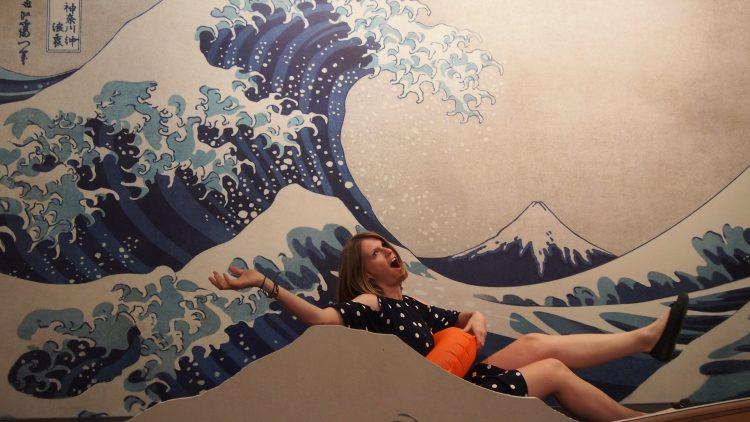 Reporterin surft in einer Welle mit Rettungsring