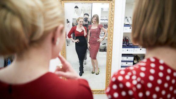 Marlene und Reporterin gucken sich im Spiegel ihre Kleider bei der Anrpobe an.