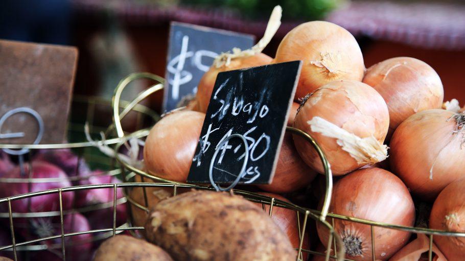 """Weiße und Rote Zwiebeln liegen in einem Metallkörbchen mit der Aufschrift """"Seboja"""""""
