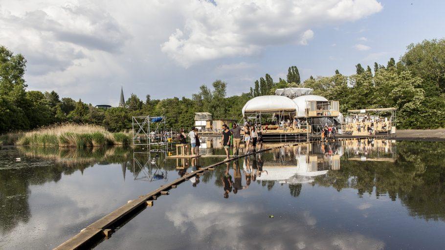 Menschen balancieren auf schmalen Steg zum Auditorium der Floating University