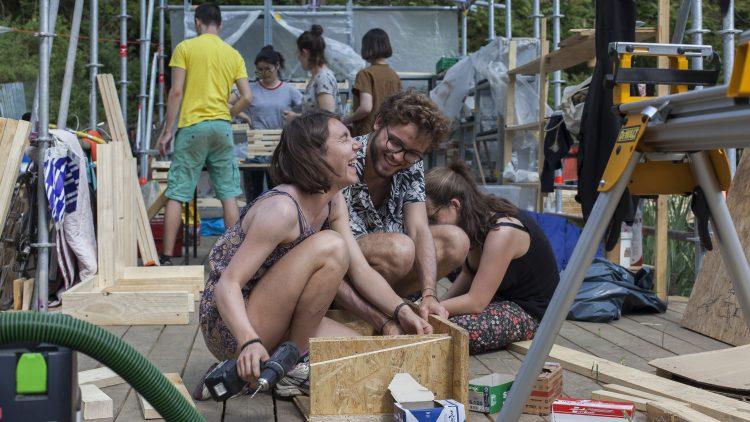 Junge Menschen sitzen auf dem Boden lachen und bauen mit Holz