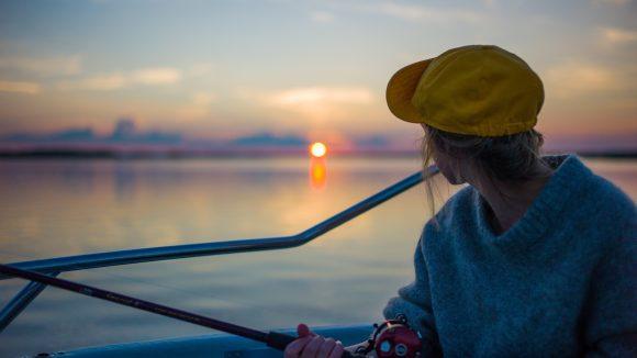 Junge Frau sitzt auf einem Boot und angelt im Sonnenuntergang.