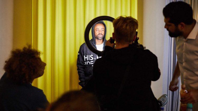 Ein Coach bei After School Hustle erklärt Jugendlichen den Umgang mit der Kamera an einem Model vor einem gelben Vorhang