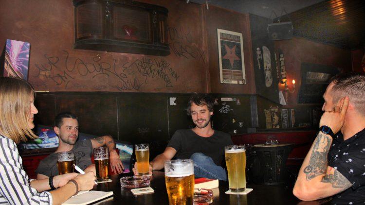 Die Band und die Journalistin sitzen mit Bier um den Tisch in einer Bar.