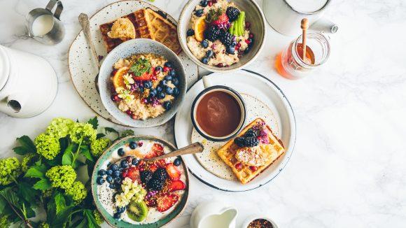 Üppiger Frühstückstisch mit Müsli, Früchten, Waffeln und Porridge