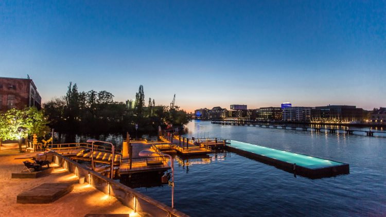 Das Badeschiff Berlin bei Abend mit Blick auf die Spree und romantischer Beleuchtung.