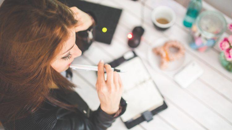 Frau mit Stift in der Hand sitzt am Schreibtisch über einen Kalender