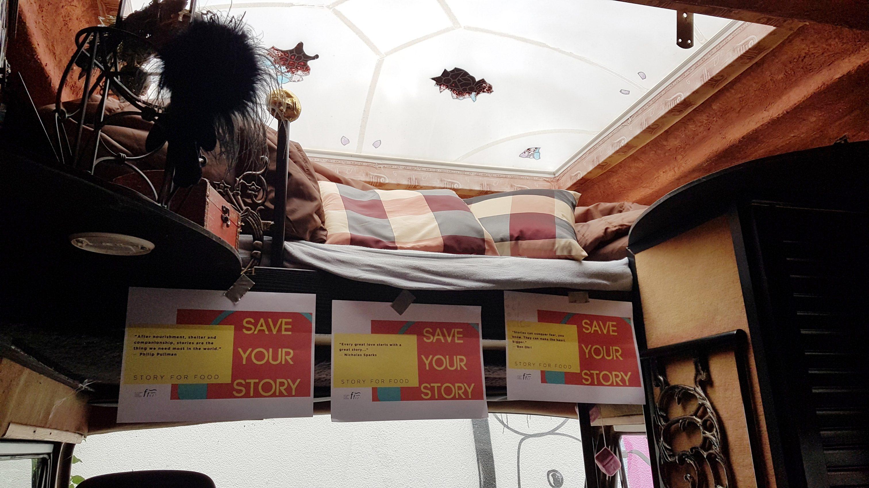 Das Innere des Vans mit dem Plakaten und einer Kuscheldecke im oberen Teil.