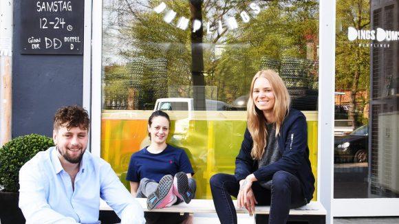 Die drei GründerInnen von DingsDums Dumplings sitzen vor ihrem Laden.