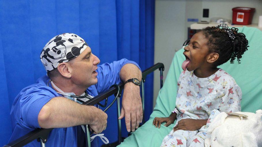 Ein Arzt kniet vor dem Bett eines farbigen Mädchens im Krankenhaus