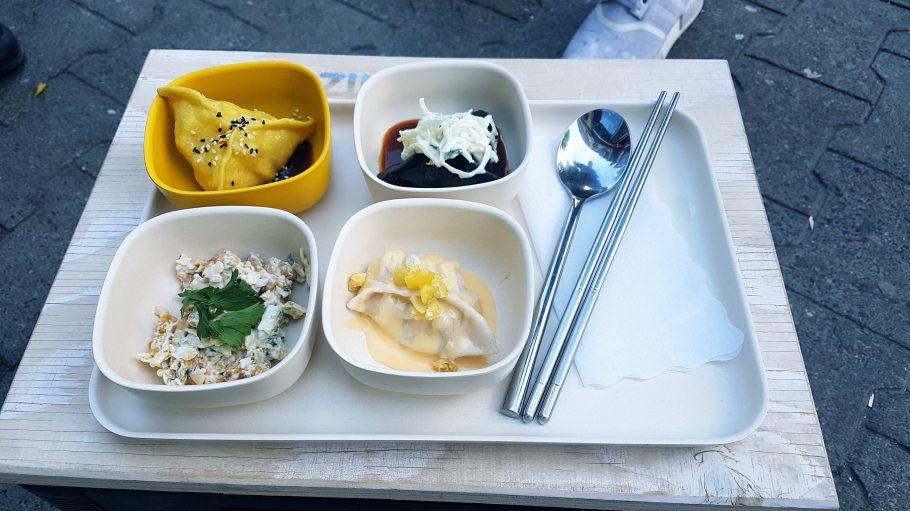 Drei verschiedene Dumplings und ein Maissalat auf einem Tablett.