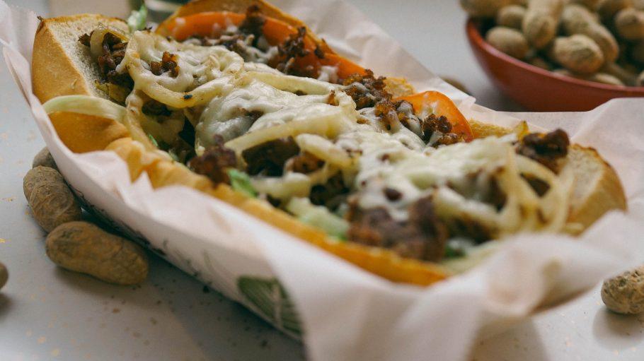 Ein Hot Dog mit farbenfrohen Zutaten gespickt