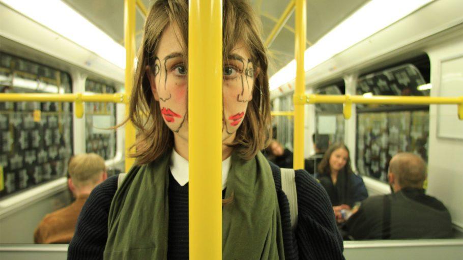 Frau in der U-Bahn mit zwei Gesichtern.