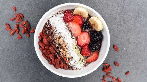 Eine Frühstücksbowle mit einem Streifen Erdbeer, Kokos, Banan und Acai.