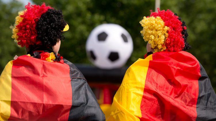 Zwei Fans mit Perücken und Deutschlandfahne von hinten